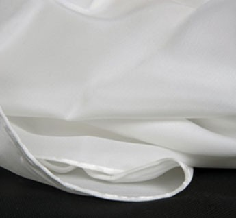 Una cara del tejido es satinada, brillante y la otra granulada, mate, de unos 50 gramos metro cuadrado. Los pañuelos, en blanco natural, están orillados a mano con hilo de seda.